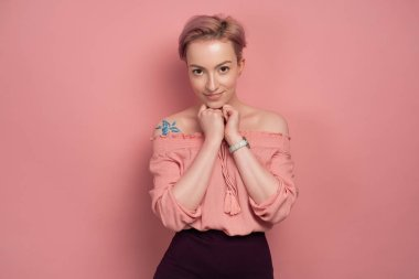 A girl with short pink hair stands on a pink background, smiling cute, looking at the camera, clutching her hands to her chest.