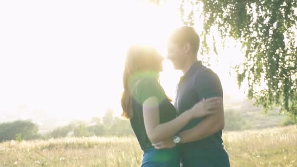 young loving couple in nature in summer on a background of leaves , there is noise on the video