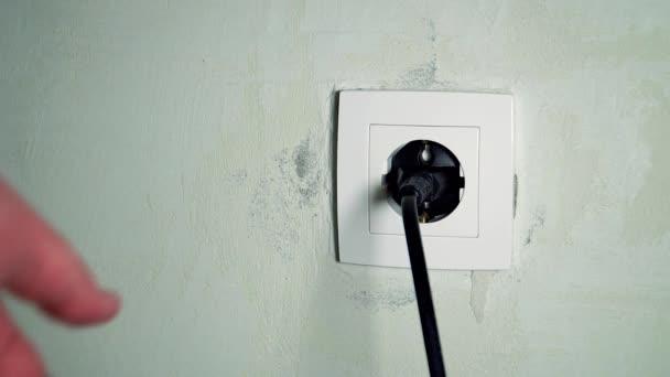 A férfi kéz kihúzta a dugót a konnektorból.