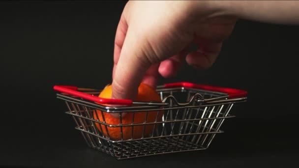 ručně dává ovoce do malého koše ze supermarketu na černém pozadí