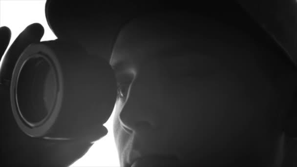 Detail silueta mladík fotograf hledá prostřednictvím objektivu fotoaparátu. Zpomalený pohyb, skica, izolované