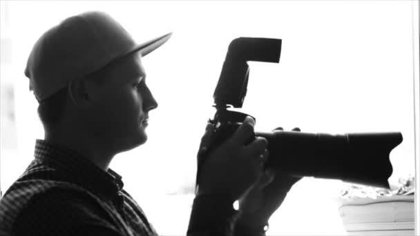 Schwarz-weiße Silhouette eines jungen männlichen Fotografen mit Schirmmütze, der mit einer professionellen Kamera fotografiert. Zeitlupe.