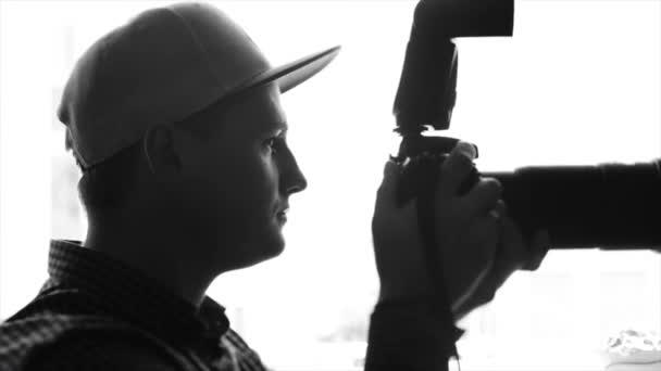 Schwarz / weiß Silhouette eines jungen männlichen Fotografen in Kappe fotografieren mit einer professionellen Kamera. Slow-motion
