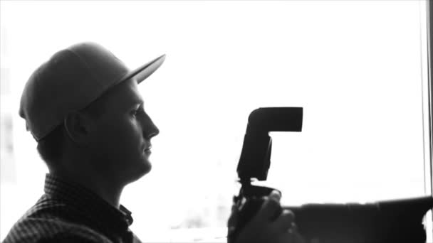 Black and white silhouette of a young male photographer in cap taking pictures with a professional camera and telling models how to pose. Slow motion.
