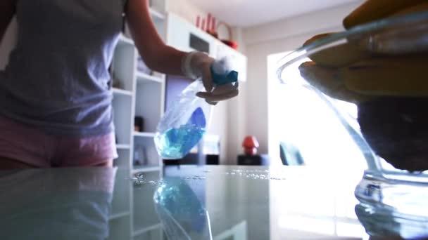 Hausfrau Reinigungsmittel sprühen und abwischen einen Glastisch