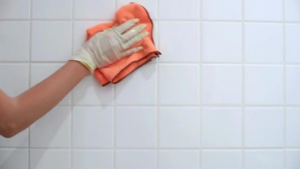 Közeli női kéz, takarítás a piszkos fehér fürdőszoba csempe