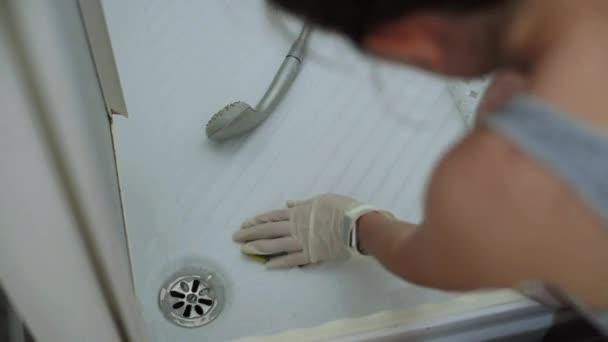 Detail hospodyňka rukou s rukavicemi čištění jímky sprcha