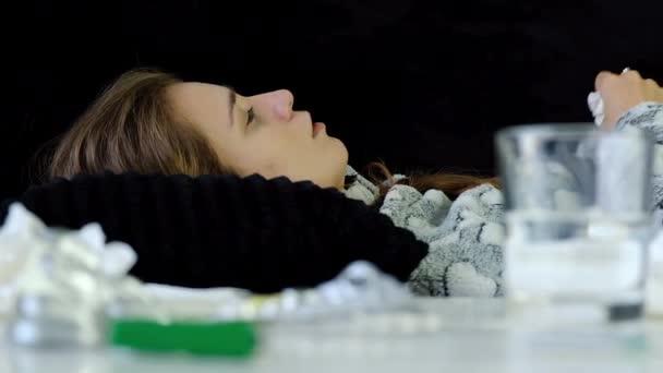 Nahaufnahme der jungen kranken Frau mit Grippe und Fieber Niesen und Blasen ihrer Nase. Medikamente auf dem Tisch.