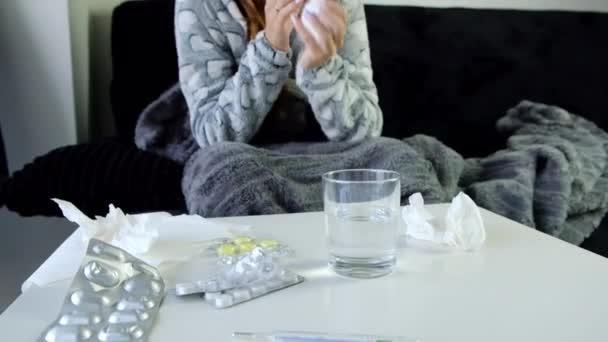 Zeitlupe einer jungen kranken Frau, die zu Hause auf dem Sofa sitzt, hustet und die Nase pustet. Medikamente auf dem Tisch.
