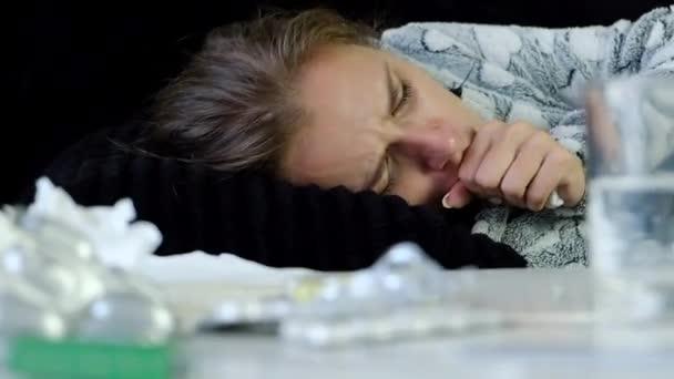 Nahaufnahme der junge kranke Frau mit Grippe und Fieber Husten schlecht. Arzneimittel auf dem Tisch.