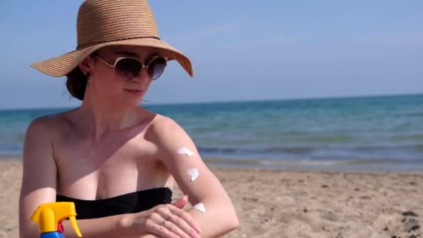 Beautiful sexy young woman applying sunscreen to arms at the beach wearing bikini and straw hat. Girl pulverizing sun protection cream from blue bottle. 4k video.
