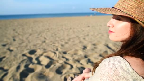 Young woman wearing straw hat relaxing on the beach