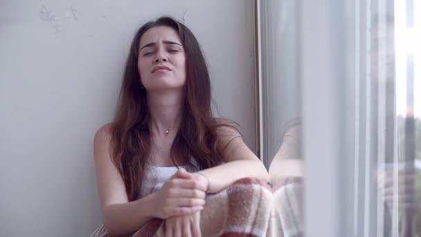 Depressziós nő sír ült a földön, az ablak kívül esik az eső. Magányos nő a kétségbeesés és az öngyilkossági gondolatok.