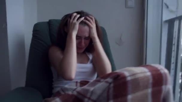 Fiatal depressziós nő húzza a haját a kezével, és sírva ült az ablak mellett. Esik az eső kívül. Magányos nő a kétségbeesés és öngyilkossági gondolatok.