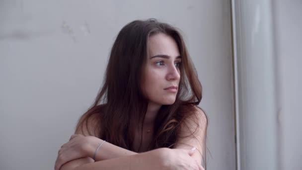 Fiatal, szomorú, depressziós nő ül a földön, és kinézett az ablakon. Magányos nő a kétségbeesés és az öngyilkossági gondolatok