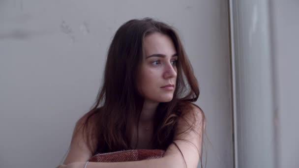 Fiatal, szomorú, depressziós nő ül a földön, és kinézett az ablakon. Magányos nő a kétségbeesés és az öngyilkossági gondolatok.