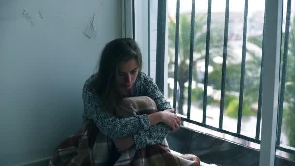 Depressziós nő ül a földön, az ablak kívül esik az eső. Magányos nő a kétségbeesés és az öngyilkossági gondolatok