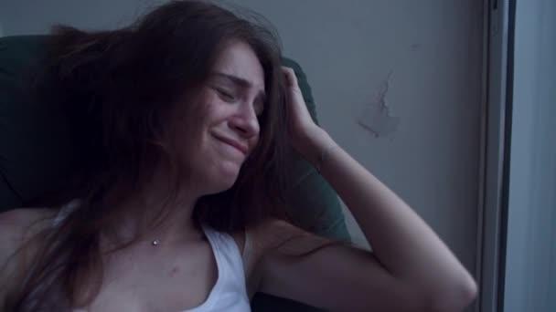 Lassú mozgás fiatal depressziós nő a baj húzza a haját a kezével, és sírva ül a székre. Magányos nő a kétségbeesés és öngyilkossági gondolatok.