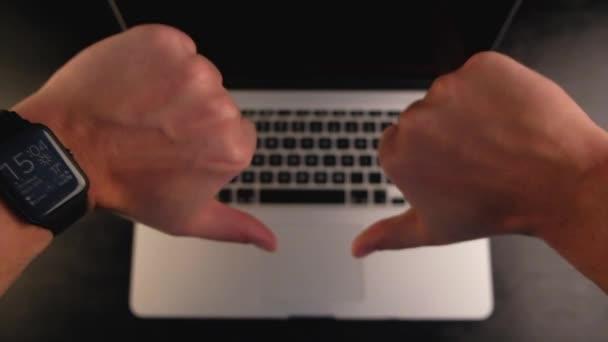 Detail člověka rukou ukazuje palcem nahoru nebo jako gesto s notebookem na černém pozadí.
