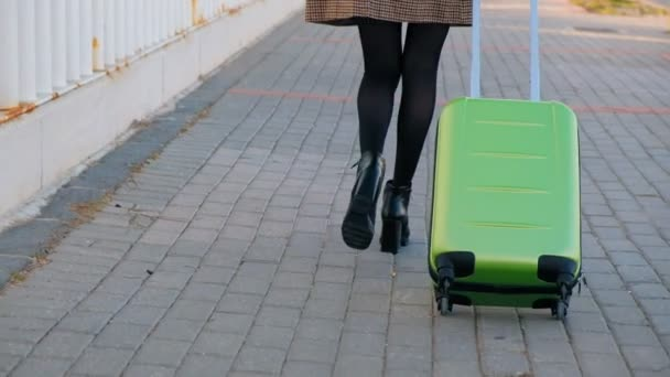 Pohled mladé obchodní ženy na vysoké podpatky na autobusovém nádraží. Stylová žena s kufrem projíždějící autobusovou zastávkou.