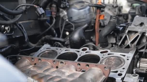 Car engine repair. Close-up of mechanic hands cleaning the car engine cylinder head after grinding.