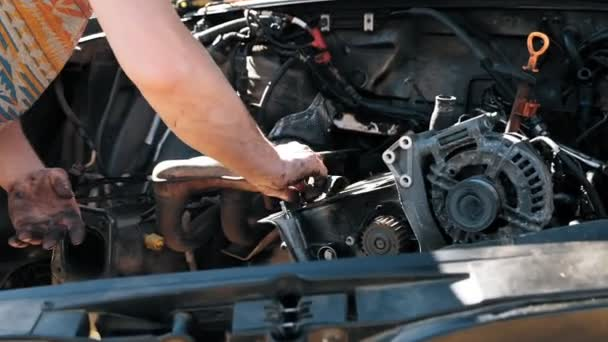 Close-up of auto mechanic greasy hands with a wrench repairing car motor. Car repair auto service. Slow motion.