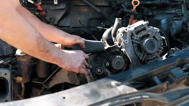 Close-up of auto mechanic greasy hands repairing car engine. Car repair auto service. Slow motion.