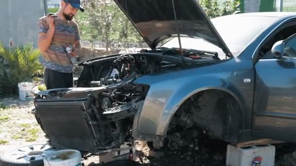 Slow motion of young bearded auto mechanic repairing disassembled car outdoors. Car repair auto service.