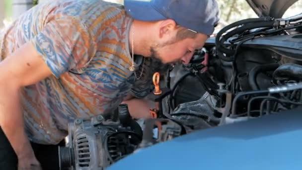 Pomalý pohyb mladý vousatý mechanik s klíčem k opravě motorového automobilu. Automatická oprava aut.