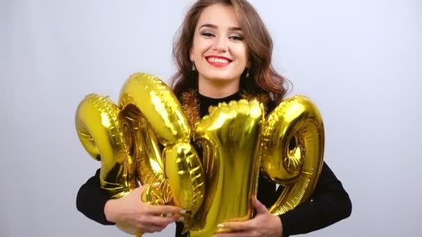 Boldog lány gazdaság arany 2019 léggömbök és mosolyogva. Lassított. Új év és karácsonyi koncepció.