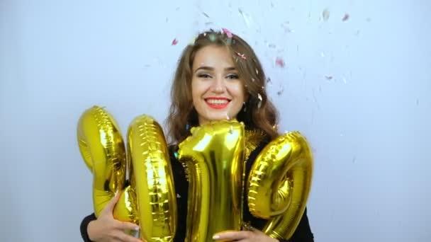 Boldog lány, aki arany 2019 léggömbök és színes konfetti zuhan. Lassított. Új év és karácsonyi koncepció.