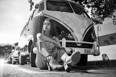 Monochrome image of woman in striped overalls posing against retro car.