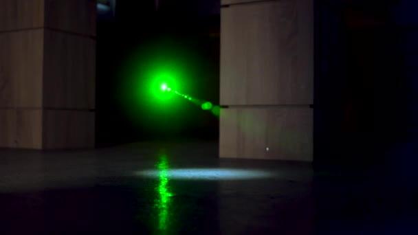 Muž zloděj na boty dělá krok snaží překonat bezpečnostní laserové paprsky pro bankovní bezpečnost, laserové bezpečnosti ontinuous vlny zelené laserové šíří prostřednictvím optické komponenty ve tmě