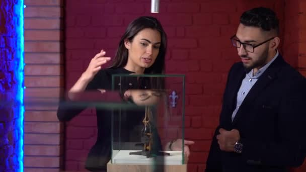 Brunette young woman guide tells to the young man in glasses about the exhibition features of the Watch by the Leonardo Da Vinci project clockwork invention
