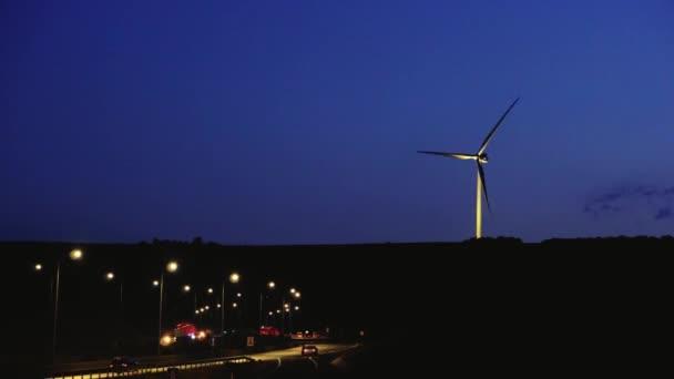 Větrné mlýny v noci soumraku nedaleko dálnice s zářící auta během provozu