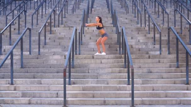Brunetka dělá podřepu ranní cvičení na schodech