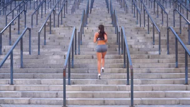 Long hair brunette girl is running up on the stairs morning exercise