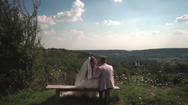 c58db05bb2 Románticos novios sentados en el banquillo en la naturaleza y ver en la  iglesia– metraje de stock