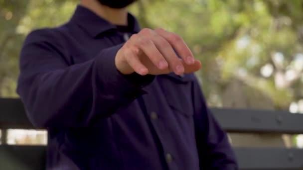 Ruka muže, který seděl na lavičce v parku muž mávl rukou ve vzduchu si představoval, že mu stiskne klávesy