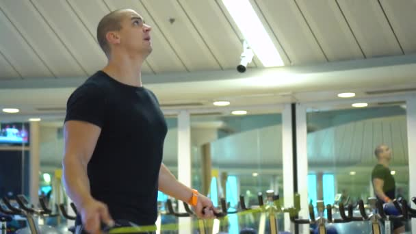 Young athletic sportsman trains with a jumping rope in gym