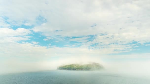 Lonely green island in Bar Harbor Maine shrouded in deep mist