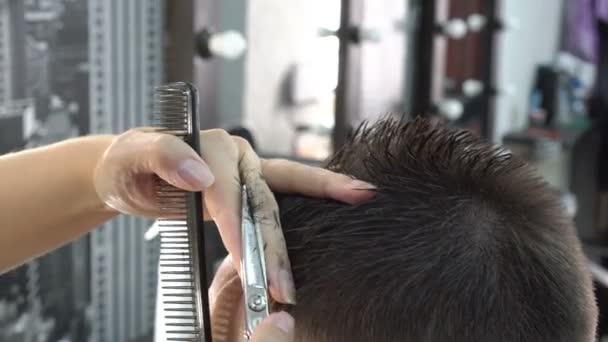 Egy ember rövid vágott haj a fejét egy fodrász boltban ollóval. Fodrász a haj teszi. Oldalnézet. Közelkép, nagy részletességgel. 4k, 25 fps