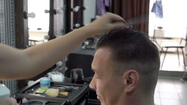 Kadeřník dělá vlasy styling muž v holičství. Lak ve spreji na jeho vlasy a češe ho. Boční pohled. Detail, Obsahové látky. 4k, 25 snímků / s