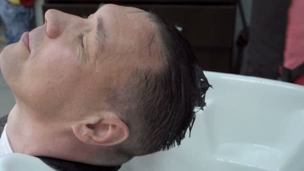 A female stylist washes a man's head in the Spa over the sink with shampoo. Hair care. Close-up, high detail. 4K, 25 fps