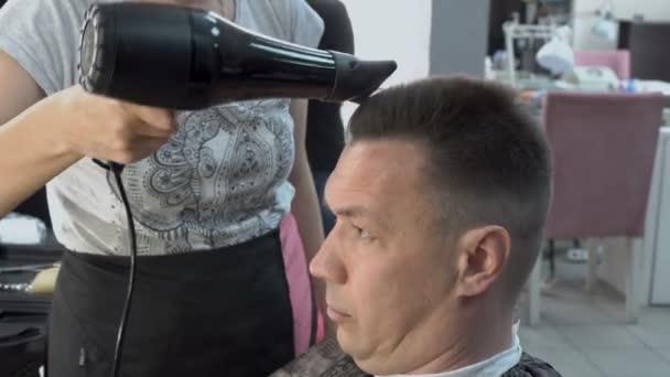 Kadeřník vysouší vlasy dospělého člověka fén v holičství a dělá mu vlasy na hlavě. Péče o vlasy. Zblízka. Boční pohled. 4k, 25 snímků / s