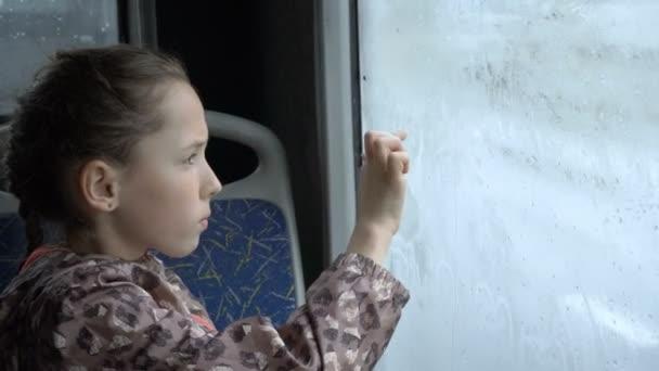 Ein kleines Mädchen sitzt im Bus auf dem Rücksitz und zeichnet Bilder mit dem Finger auf dem nassen beschlagene Glas. Außerhalb der Fenster Auto fahren. Porträt. Hautnah. Mit hohem Detailgrad. 4k, 25 fps