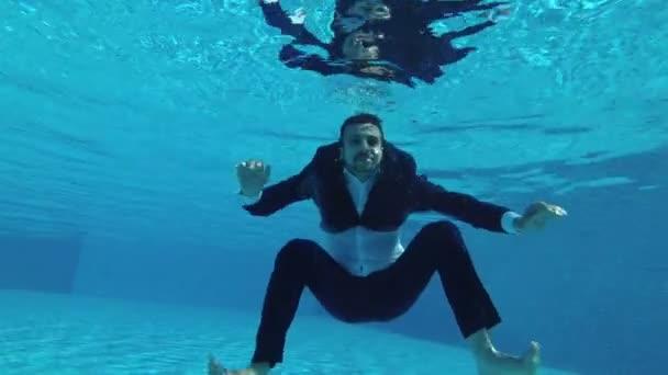 Ženich v obleku plave a představuje pod vodou v bazénu. Se dívá na fotoaparát, vlny ruce a úsměvy. Zpomalený pohyb. Akční kamery pod vodou. 4k, 25 snímků / s