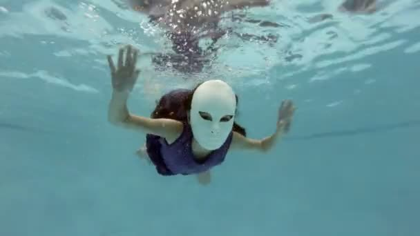 A little girl in a fabulous white mask swims and poses under the water, looks at the camera and waving his hands. 4K.
