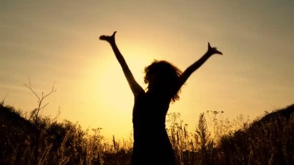 die Silhouette eines Mädchens, das auf einem gelben Sonnenuntergang in einem Feld zwischen den Blumen zwischen den Hügeln springt. Ansicht von unten. Nahaufnahme. 4k. 25 fps