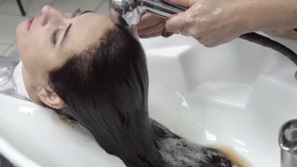 Žena myje hlavu a smyjte hnědé barvy z její vlasy po barvení procedury v salonu krásy. Péče o vlasy. Zblízka. 4 k. 25 snímků / s